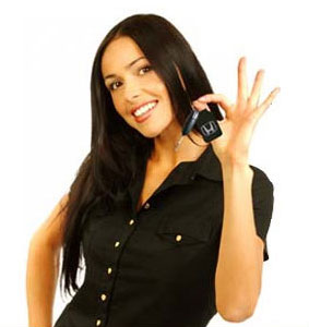 A smiling woman holding up car keys.