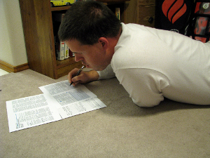 A man lying on the floor as he fills out important tax papers.