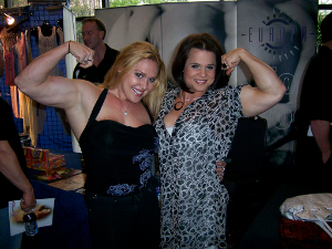 Two female weightlifters flex for the camera.