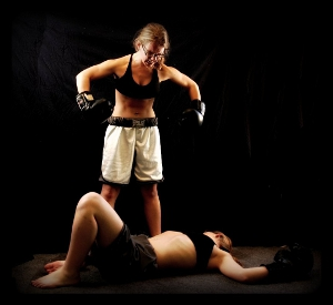 An angry female boxer stands over her dispatched foe on the canvas.