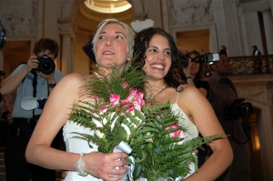 Two happily married women in wedding gowns with bouquets in hand.