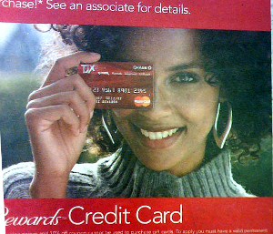 Close-up of a smiling woman in an advertisement who is holding a credit card in front of her right eye.