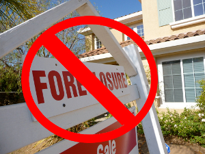 "Close-up of a street-side foreclosure sign posted for a home. There's a red cross-out over the word ""foreclosure."""