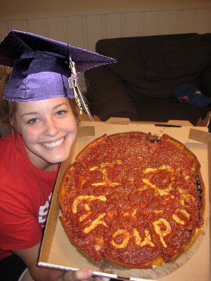 "A college student shows off a pizza with the words ""I (heart) Groupon"" written in the sauce."