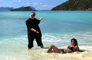 A heavyset man and a fit woman in a bikini meet on a tropical beach. A cruise ship is visible in the background.