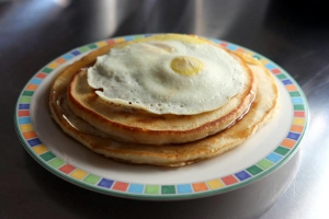 A colorful plate with pancakes and egg on top.