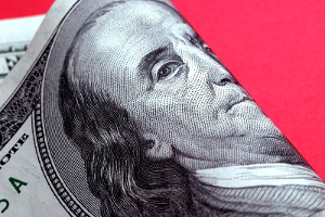 Close-up of the center of a folded $100 bill, set against a red background.