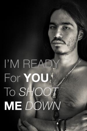 "Photo of a shirtless man. Text on the image reads, ""I'm ready for you to shoot me down."""