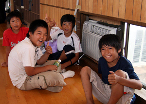 Four Japanese boys show their appreciation for the newly installed air conditioning units at the Arahama Community Center. The center received six window units, courtesy of a joint effort between the U.S. military and Japan Self-Defense Forces. Fifteen Seabees from Naval Air Facility Atsugi were sent to help in the effort to the area still reeling from the effects of a July 16 earthquake. The quake killed 10, left more than 1,200 injured, destroyed nearly 1,000 homes and damaged 4,000 others.