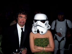 A man and his female roommate, who is wearing a Star Wars stormtrooper helmet.