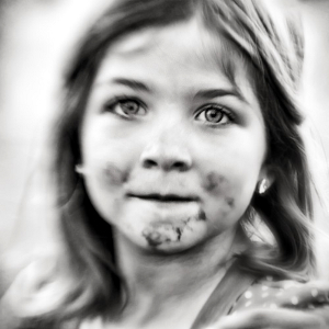 Black-and-white photo of a little girl with chocolate smudges around her mouth.