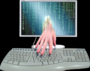 A hand reaching out from a computer screen to type on a keyboard.