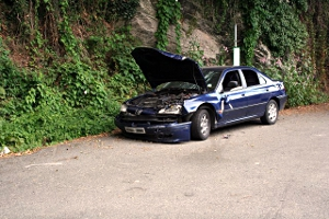 A wrecked, broken-down car at the side of the road.