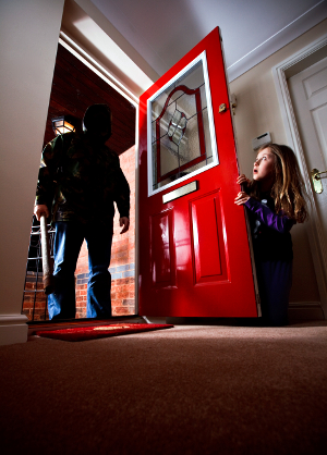 A dark, shadowy figure in the doorway frightens a diminutive young girl.