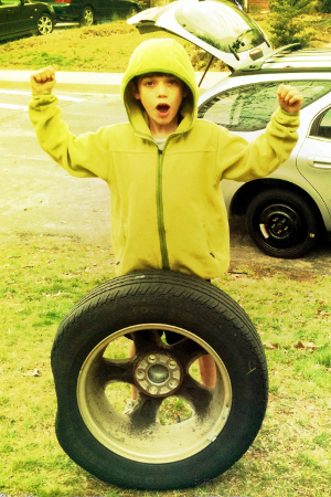 A boy changing a spare tire.